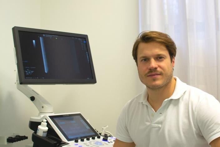 Dr. Florian Wenzel-Schwarz im Portrait in seiner Ordination Ortho am See in Neusiedl am See neben einem Ultraschallgerät