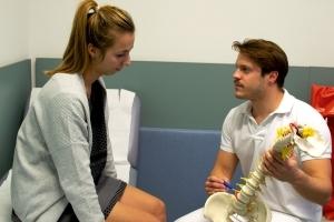 Dr. Florian Wenzel-Schwarz erklaert in seiner Praxis Ortho am See in Neusiedl am See einer Patientin Stuetzapparat