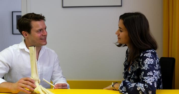 Dr. Florian Wenzel-Schwarz erklärt einer Patientin die Anatomie des Fusses
